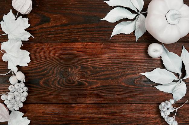 Citrouille blanche, baies et feuilles sur un fond d'automne en bois