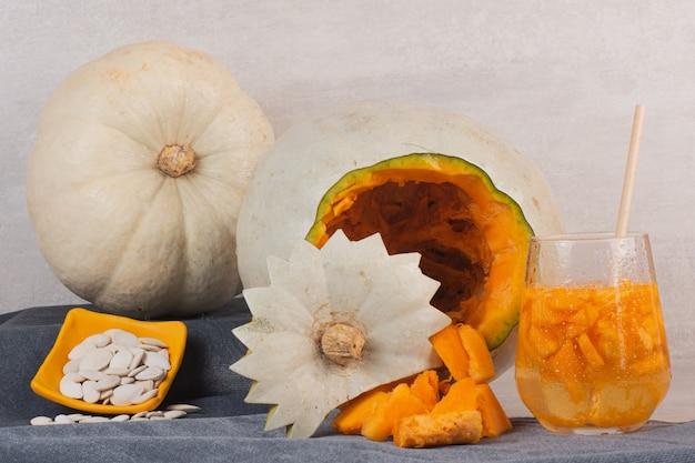 Citrouille blanche, verre de jus et graines de citrouille sur table blanche.