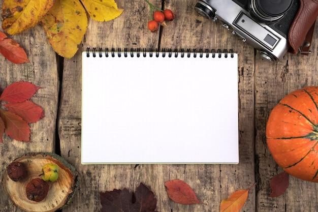Citrouille, bloc-notes, appareil photo, feuilles d'automne et baies sur une table en bois naturel.