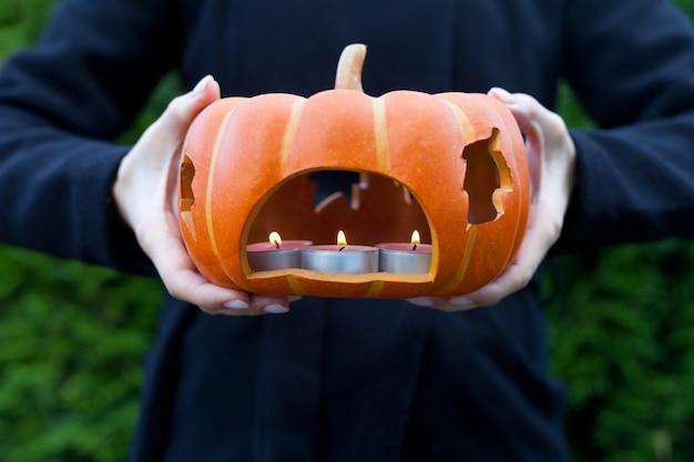 Citrouille avec bougie sur les mains de la femme près de la décoration d'uphalloween et du concept de personnes