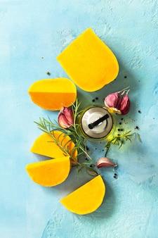 Citrouille crue avec des épices à l'huile d'olive et des ingrédients pour la cuisson vue de dessus à plat