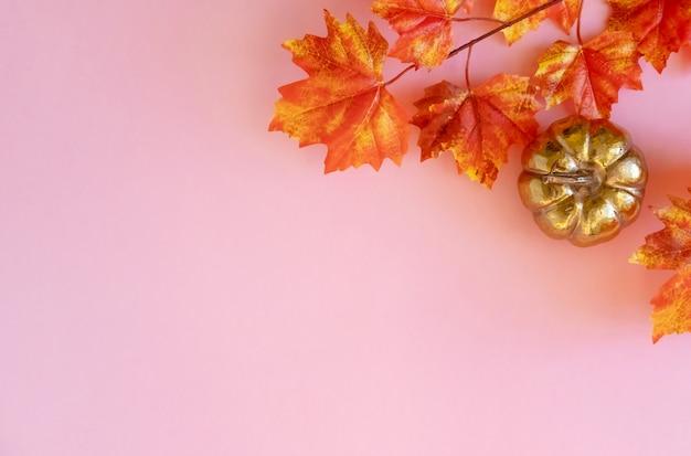 Citrouille dorée avec un maple leafs sur fond rose. lay plat.