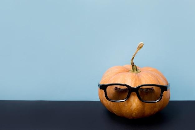Citrouille avec faux cils et lunettes de soleil sur fond bleu, halloween