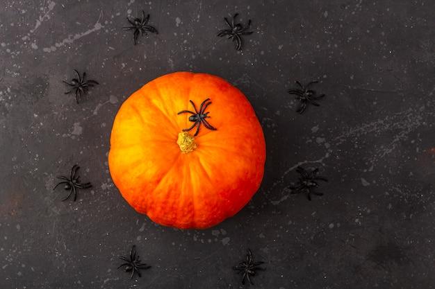 Citrouille d'halloween avec des araignées autour d'elle sur un bacground sombre