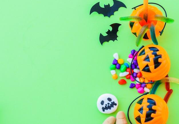 Citrouille d'halloween avec des bonbons bonbons sur fond vert