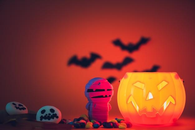 Citrouille d'halloween avec des bonbons et des bonbons à la guimauve fantôme.