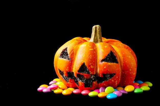 Citrouille d'halloween avec des bonbons sur un fond noir.