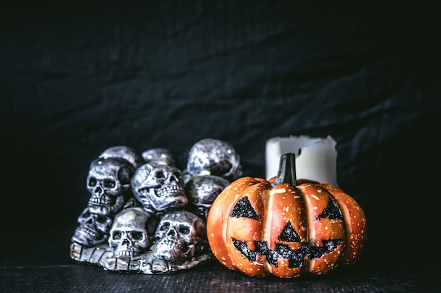 Citrouille d'halloween avec des crânes et des bougies sur un fond noir.