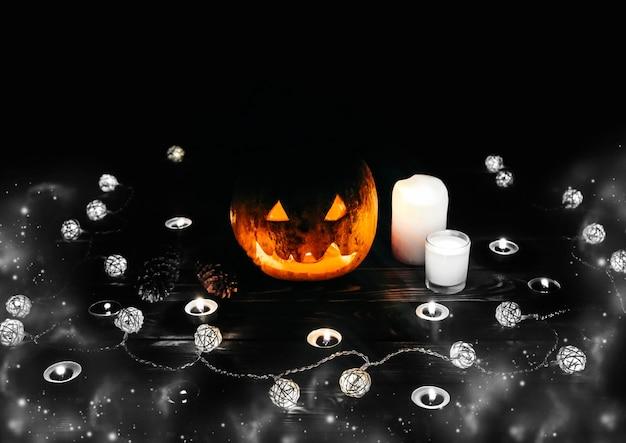 Citrouille d'halloween dans l'obscurité. allume des lampes et des bougies. vacances d'automne mystiques. détails festifs. la tradition des bonbons ou un sort. toussaint en octobre.