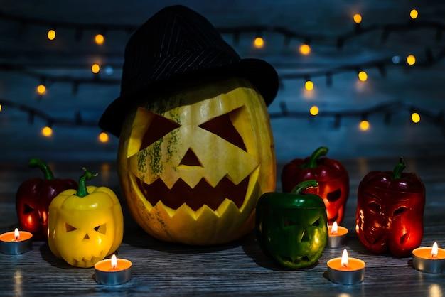 Une citrouille d'halloween effrayante au chapeau avec une cicatrice sur le visage et des poivrons colorés aux visages coupés attendent la célébration. guirlande lumineuse sur le fond