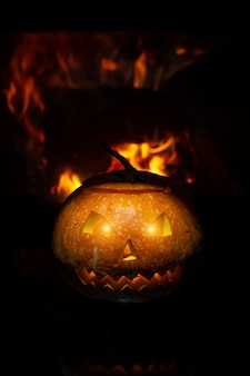 Citrouille d'halloween effrayante près d'une cheminée. feu sur le fond.