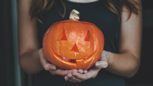 Citrouille d'halloween entre les mains d'une fille avec des lumières du bengale. concept de vacances halloween. belle femme avec des citrouilles.