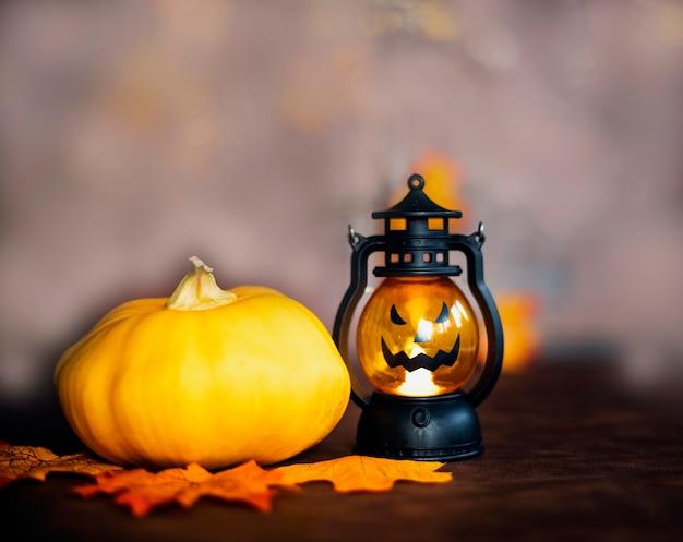 Citrouille d'halloween sur les feuilles d'automne et jack o lantern sur la texture de fond en bois marron halloween