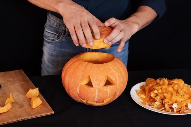 Citrouille d'halloween. l'homme prépare la décoration traditionnelle pour la célébration