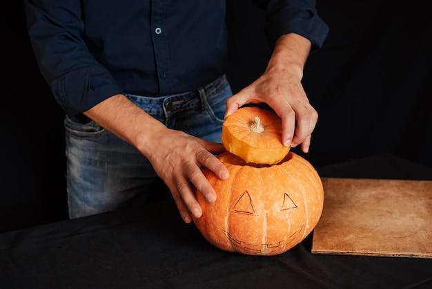 Citrouille d'halloween, l'homme prépare une décoration traditionnelle pour la célébration