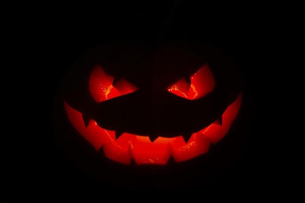 Citrouille d'halloween jack-o-lantern sur fond noir