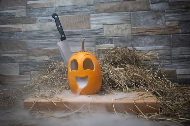 Citrouille d'halloween jaune et drôle avec un couteau dans la tête et de la fumée ou de la vapeur de sa bouche