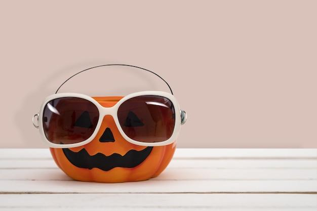 Citrouille d'halloween avec des lunettes sur fond rose. idée minimale d'halloween