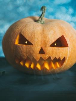 Citrouille d'halloween avec visage effrayant sur l'obscurité