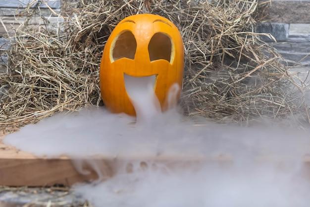 Citrouille heureuse jaune et très drôle pour la célébration d'halloween avec beaucoup de fumée ou de vapeur de la bouche