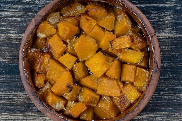 Citrouille jaune au four avec du miel, de l'huile d'olive et des épices sur une assiette sur la table en bois. la nourriture végétarienne. fermer