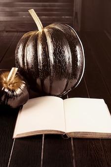 Citrouille noire et livre ouvert. décoration de la maison pour halloween dans le style moderne. verticale.