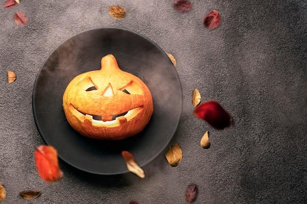 Une citrouille orange effrayante sur la table, des yeux brillants, une assiette noire et un arrière-plan. invitation à une fête d'halloween dans un restaurant ou à une célébration dans une carte de bar.