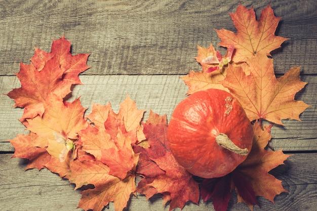 Citrouille orange et feuilles d'érable sur planche de bois. modèle d'automne.
