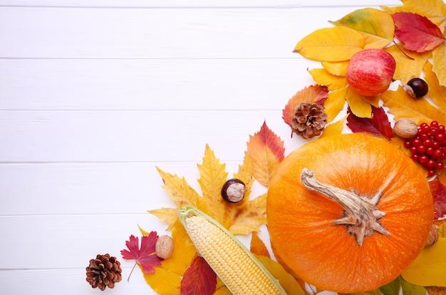 Citrouille orange avec des feuilles et des légumes sur blanc