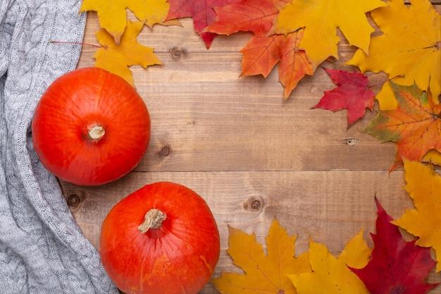 Citrouille orange, pull confortable, feuilles d'érable sur le concept de l'automne en bois
