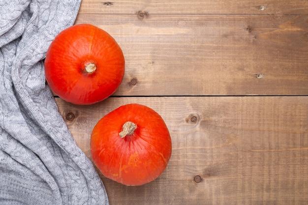 Citrouille orange, pull sur fond en bois. style rustique. notion d'automne. vue de dessus. espace de copie
