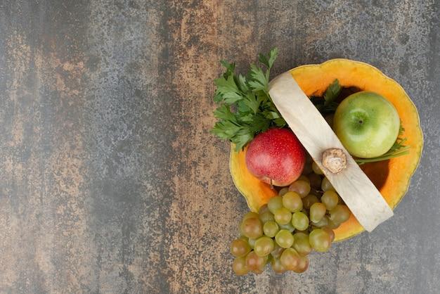 Citrouille pleine de pommes et de raisins sur mur de marbre