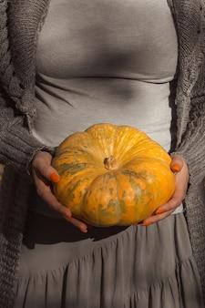 Citrouille ronde orange mûre dans les mains des femmes