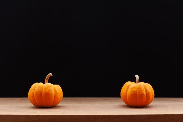 Citrouille sur table en bois avec un fond sombre. halloween et concept de décoration.