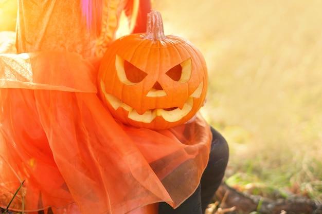 Citrouille avec un visage maléfique dans les mains d'un enfant à l'halloween