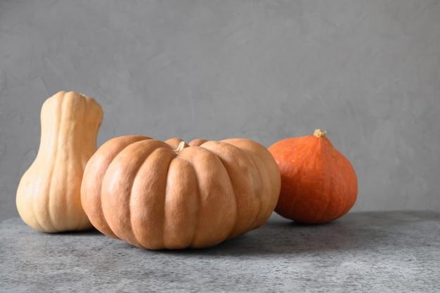 Citrouilles biologiques sur fond beige récolte d'automne pour le jour de thanksgiving ou la fête d'halloween