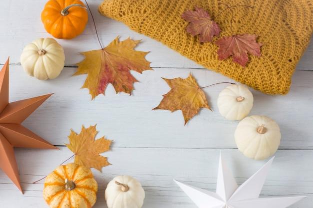 Citrouilles blanches et oranges, une couverture orange tricotée, feuilles d'automne