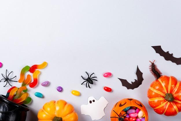Citrouilles, bonbons, fantômes, araignées, chauves-souris et mille-pattes sur gris.