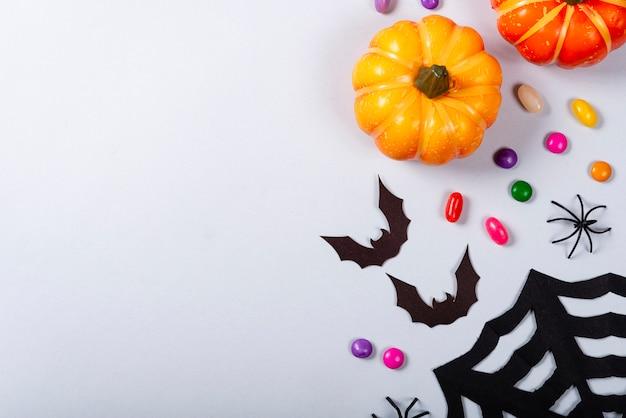 Citrouilles, bonbons, toile, chauves-souris et araignées sur fond gris.