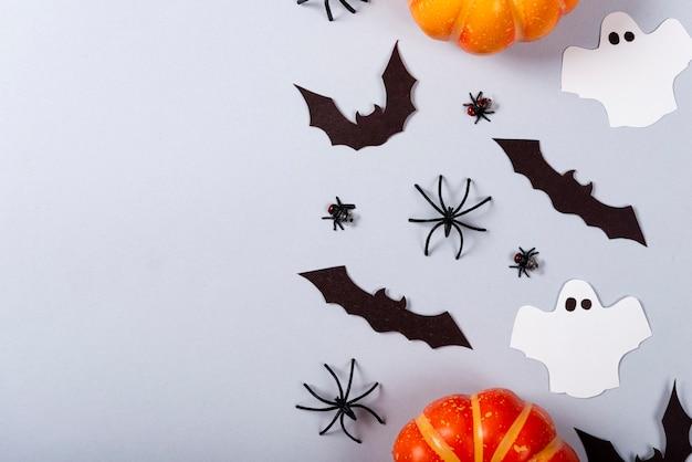 Citrouilles, chauves-souris, mouches, araignées et fantômes sur fond gris.
