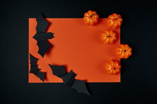Citrouilles décoratives et chauves-souris en papier sur fond noir et orange. concept de vacances d'halloween. mise en page à plat, flatley