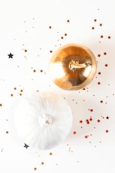 Citrouilles décoratives dorées et blanches sur fond clair parmi les étoiles d'or