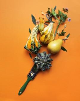 Citrouilles décoratives, feuilles vertes, fleurs, une poire et un pinceau sur fond orange.la composition automne créative à plat