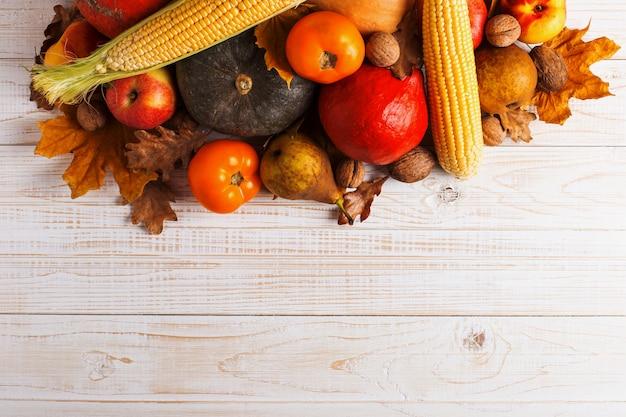 Citrouilles de différents légumes, pommes, poires, noix, maïs, tomates, feuilles jaunes sèches sur fond en bois blanc. récolte d'automne, surface.