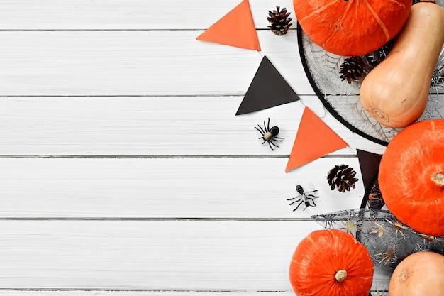 Les citrouilles du jour d'halloween et les araignées de sorcières d'attirail d'halloween sont allongées sur un tableau blanc