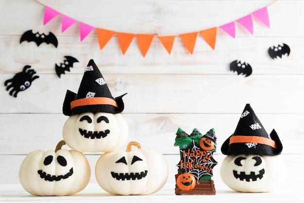 Citrouilles fantômes blancs avec chapeau de sorcière sur fond de planche de bois blanc avec batte.