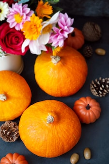 Citrouilles fraîches. flatlay créatif d'automne, fond sombre avec des bougies, des fleurs d'automne, des pommes de pin et des citrouilles. vue de dessus.