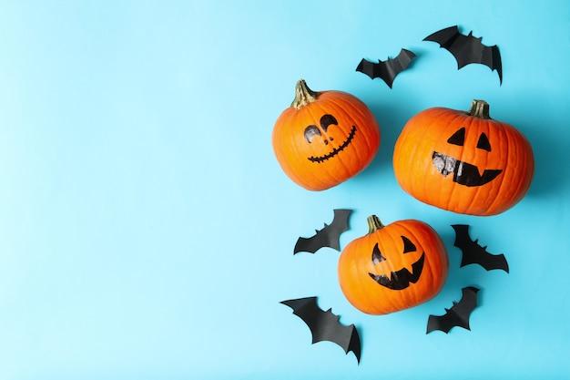 Citrouilles d'halloween et chauves-souris en papier sur bleu
