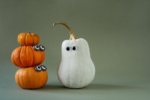 Citrouilles d'halloween drôles avec des yeux écarquillés sur vert
