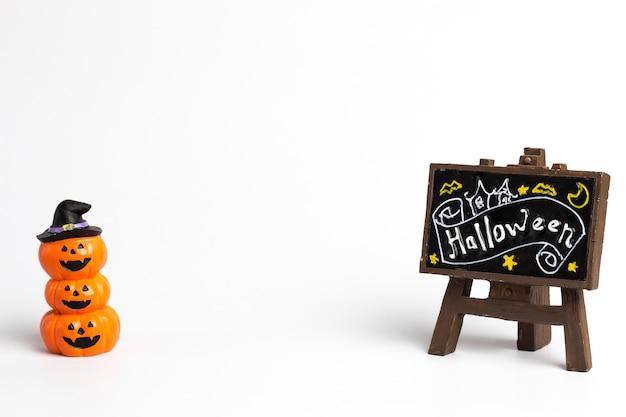 Citrouilles d'halloween empilés trois balles et une étiquette brune avec du texte d'halloween.